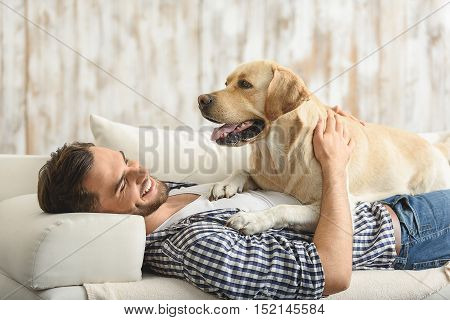 big dog resting on a belly of a smiling guy at home