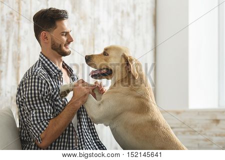 handsome bearded human playing with his dog indoors