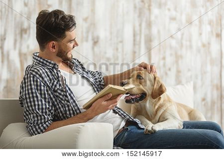 handsome man petting his dog while holding a book on a couch