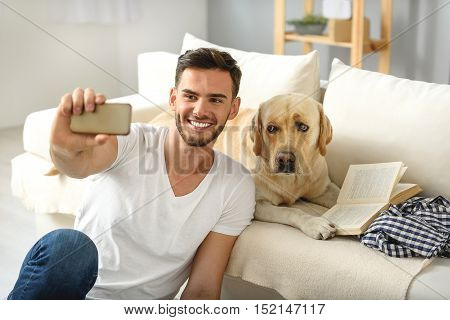 annoyed puppy looking at smartphone while boy taking selfie