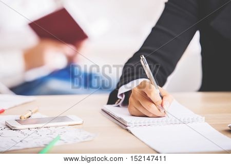 Closeup of businesswoman hand writing in spiral notepad placed on wooden desktop with smartphone and other items