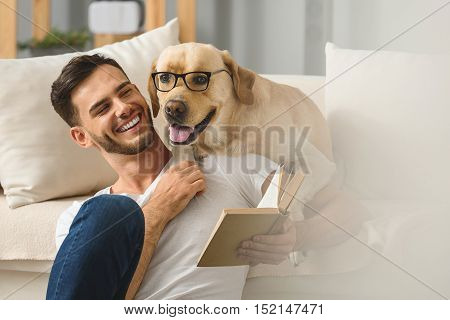 smart dog in glasses resting with its human friend on a couch