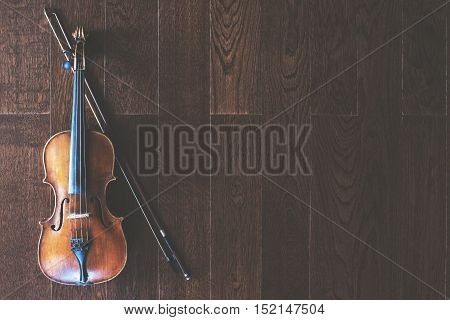 Top view of violin with bow on wooden floor with copy space
