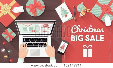 Man purchasing Christmas gifts online using a laptop on his desk shopping bags and decorations all around holiday and celebrations banner