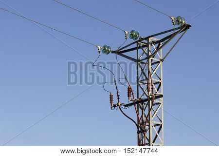 Isolated hight voltage tower in a blue cloudless sky.