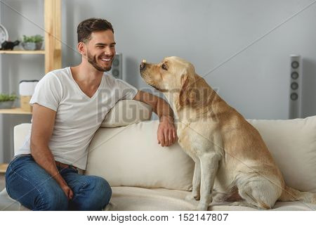 smiling bearded man training his dog with treats