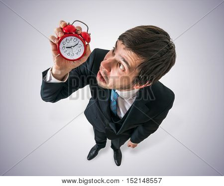 Deadline Concept. Young Stressed Man Is Looking At Clock And Hav