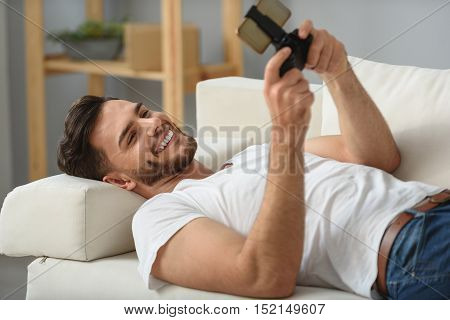 man playing games on smartphone with gamepad and smiling