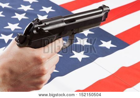 Gun In Hand With Flag On Background - United States Of America