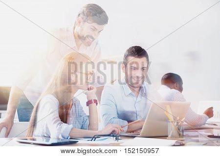 Work with pleasure. Three young workers using laptop in light modern office.