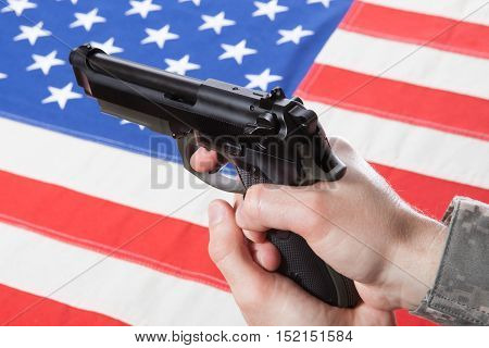 Close Up Studio Shot Of Gun In Hand With Flag On Background - United States Of America