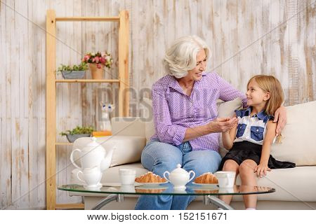 Happy old woman is having breakfast with her granddaughter. They are sitting on sofa and smiling. Family is holding hands and embracing