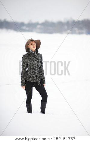 Portrait of a slender young woman in coat and hat standing in the snow on the background of snowy city in winter Park.