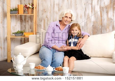 Happy family. Cheerful senior woman is embracing her granddaughter with love. They are looking at camera and smiling. Lady and girl are sitting on sofa at home