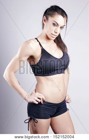 Athletic brunette woman standing preparing to fight looking down over a grey background.