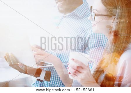 Work with smile. Cheerful young woman holding coffee cup and pointing on laptop of her partner.