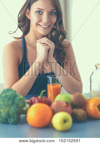 Girl sitting in kitchen on the desk with fruit and glasses with juice.