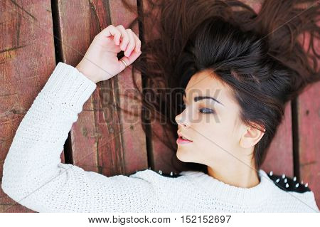 Beautiful girl with great hair lays on boards top view closeup.