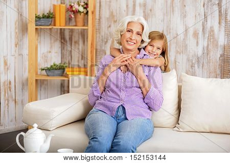 Happy little girl is embracing her grandmother with affection. Old woman is sitting on sofa and smiling