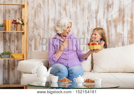 Pretty girl is greeting her granny with event. Old woman is holding gift and looking at box with surprise. She is sitting on sofa and laughing
