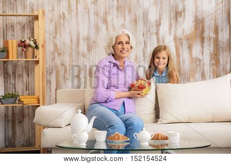 Happy grandmother is celebrating her birthday with granddaughter. She is sitting on sofa and holding gift box. Family is looking at camera and smiling