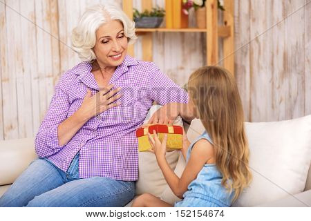 Pretty girl is giving present to her grandmother. Mature woman is sitting and looking at colored box with excitement