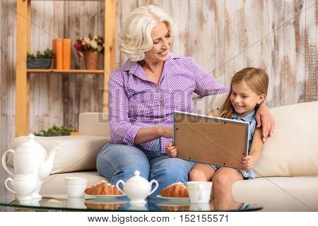 Happy grandmother and granddaughter are watching photo in frame with interest. They are sitting on sofa and smiling. Old woman is embracing girl with love