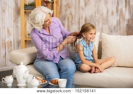 Joyful old woman is weaving braid for her small granddaughter. Girl is sitting on sofa and laughing
