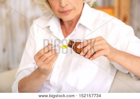 Sick old woman is pouring cough syrup into measure spoon with concentration. She is sitting on sofa at home