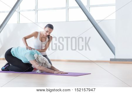 Good physical shape. Confident slim grey haired woman bending forwards and stretching out her arms while sitting on a mat