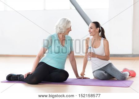 Short break between exercises. Pleasant positive cheerful women looking at each other and laughing while sitting near each other