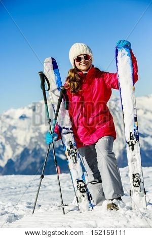 Smiling girl standing with ski and arms spreading wide open on the fresh powder snow at sunny day in mountains.