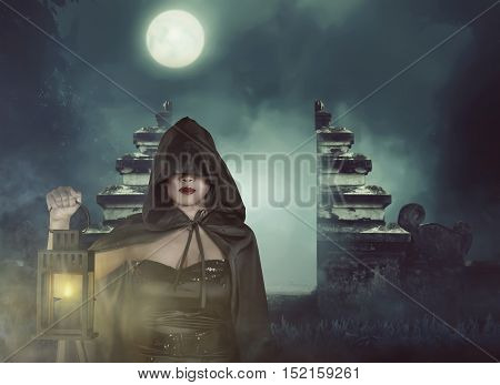 Young Asian Witch Woman In Black Corset And Cloak Hooded With Lantern
