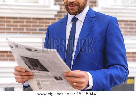 newspaper in hands of a bearded guy, close up