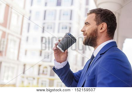 smart banker holding a cup of beverage in the city with copy space