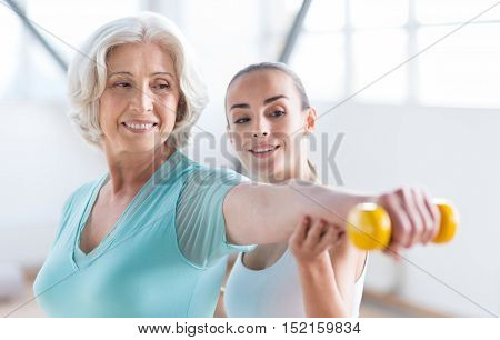 You are never too old for sport. Good looking delighted grey haired woman holding a yellow dumbbell and smiling while training with a coach
