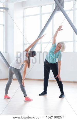 Let us do it together. Nice optimistic well built women standing opposite each other and doing physical exercises while being in a fitness club