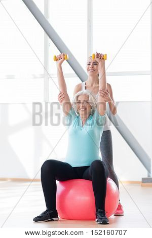 Positive attitude. Cheerful good looking grey haired woman holding her hands up and smiling while sitting on a fitness ball