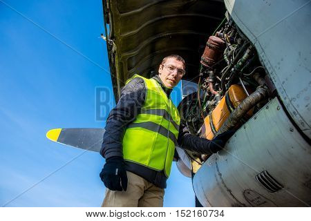 Young male mechanic fixing old airplane's engine