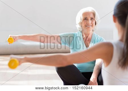 Simultaneous movements. Pleasant happy active women sitting cross legged opposite each other and raising their hands while holding dumbbells