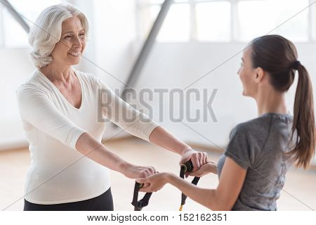Special equipment for a workout. Persistent energetic positive woman looking at her fitness coach and smiling while exercising