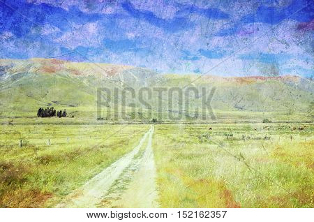 Dirt road leading through meadows to mountains in the distance. Summer in the New Zealand countryside. Grunge, vintage textured image.