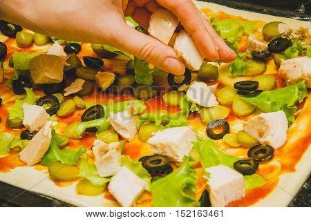 women hand prepare homemade rectangular pizza, ingredients close up