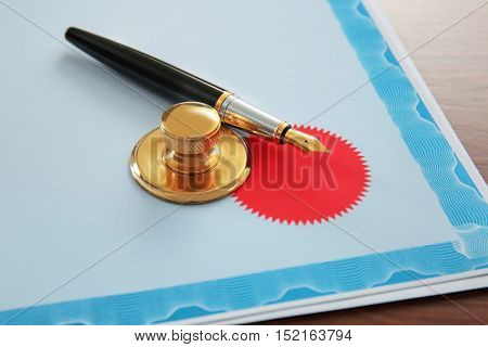 Pen, stamp and document on notary public table