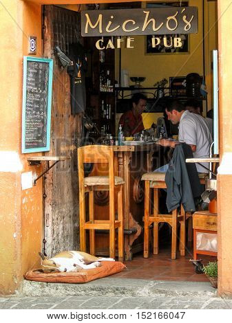 Antigua, Guatemala - June 16, 2011: Man eats at Michos café pub with a terrier dog sleeping in a dog bed on the cobble stones in Antigua, Guatemala. Editorial use only.