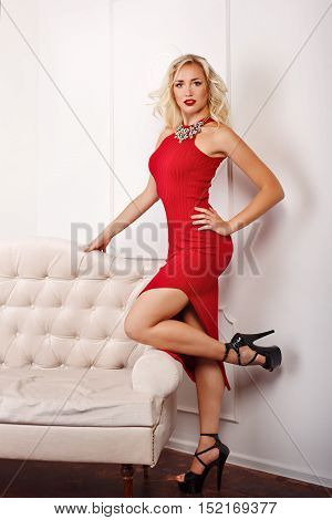 Young attractive girl in red dress and high heels. High-fashion. Girl with a necklace around her neck. The concept of selling jewelry.