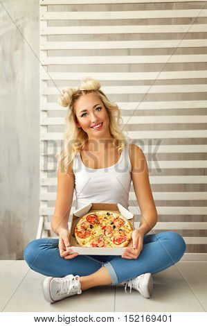 Young attractive girl holding a box with a delicious pizza. She a T-shirt and jeans sneakers sitting on the floor at home.