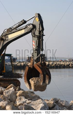 Boulders being positioned to strengthen a coastal sea wall, defense against rising sea levels due to global warming.
