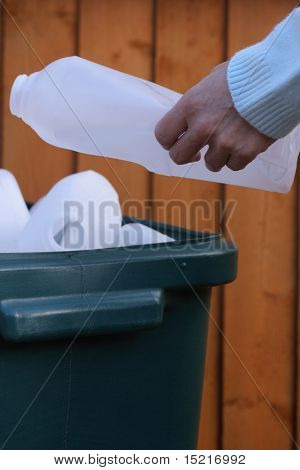 Plastic bottle being placed into a tub to be recycled environmental issues