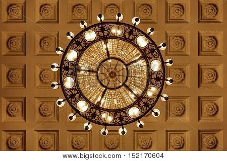 Chandelier on decoarted ceiling of a ballroom